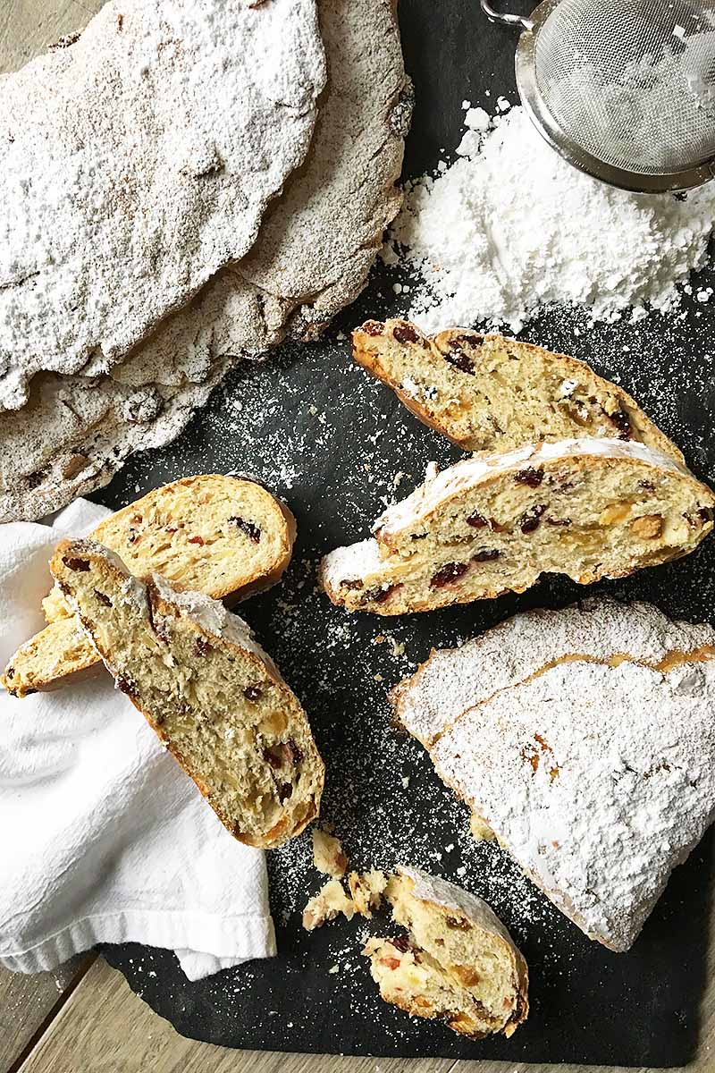 Vertical image of whole and sliced stollen on a slate scattered with powdered sugar.