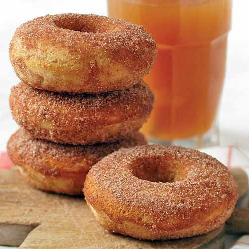Closeup of a stack of three apple cider doughnuts coated in cinnamon sugar with one more in the foreground, and a glass of cider in the background.