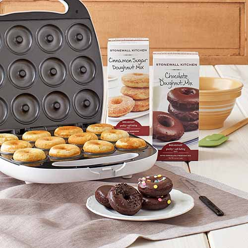 Stonewall Kitchen doughnut maker and assorted mixes, with a plate of chocolate doughnuts in the foreground on a gray cloth.