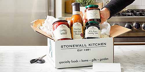 A cardboard box filled with Stonewall Kitchen dressings, jams, and sauces, on a kitchen counter with a pair of scissors, and a stove in the background.