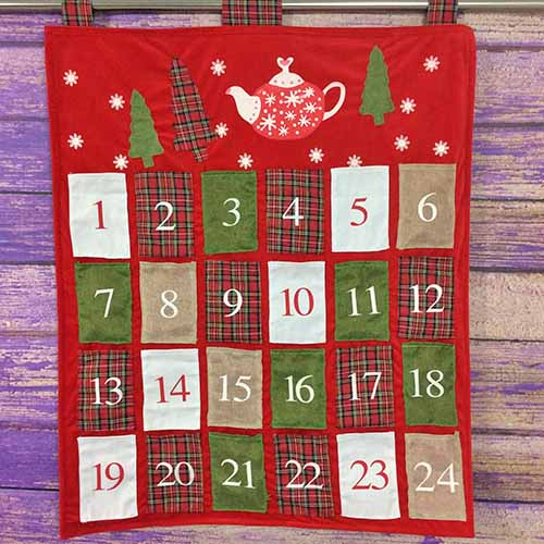 Square image of a red, white, and green fabric advent calendar hanging decoration for the wall, with a teapot and decorative Christmas trees and polka dots, with pockets numbered for each day of December, on a stained purple wood background.