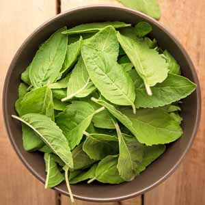 Top down view of a wooden bowl full of fresh Thai basil leaves.