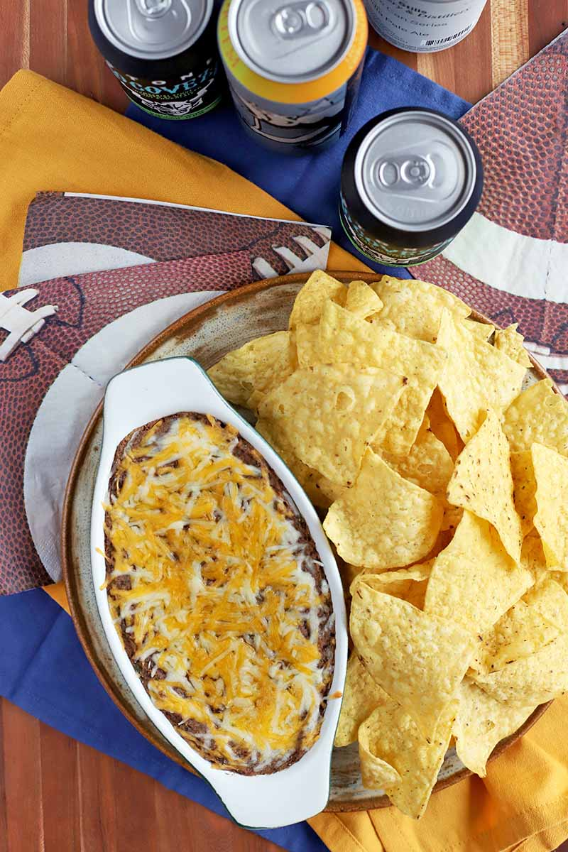 Overhead vertical shot of an oval-shaped ceramic baking dish filled with black bean dip topped with melted cheese, beside a plate of yellow corn chips, on top of football-themed and blue and yellow paper napkins with several beverage cans, on a brown surface.