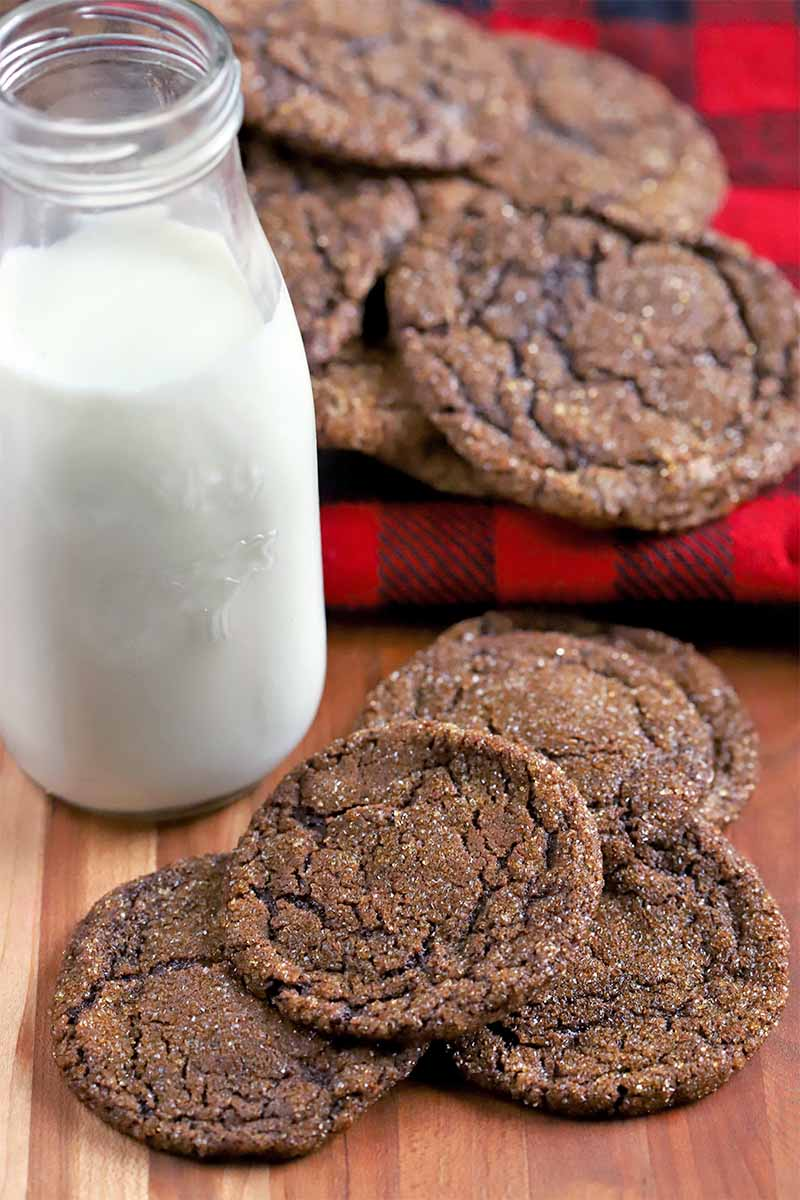 Nine dark chocolate cookies are arranged in two piles on a red and black folded flannel cloth and a brown surface, with a glass bottle of milk.
