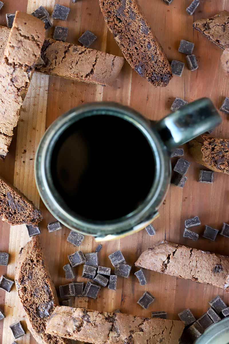 Overhead shot of a green mug of coffee, biscotti cookies, and scattered chocolate chunks on a brown wood background.
