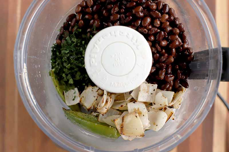 Overhead shot of a KitchenAid food processor canister filled ith black beans, roasted jalapeno and onion, and minced fresh green herbs.