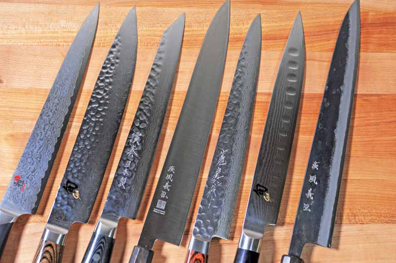 Top-down view of seven different Japanese Sujihiki slicing knives on a maple butcher block surface. The blades are all lined up and slanted at a diagonal to the right of the frame.