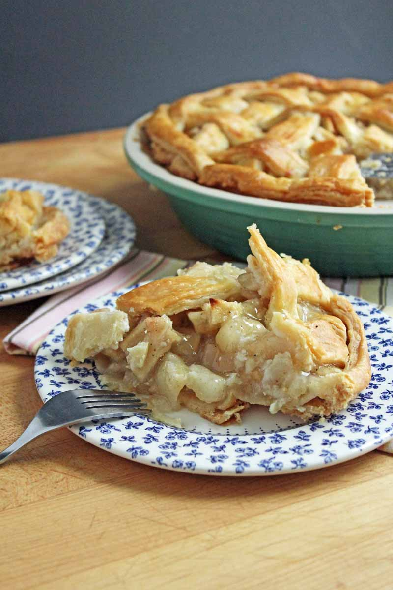 A slice of apple pear pie on a white and blue patterned porcelain plate with the remainder in a dish in the background.