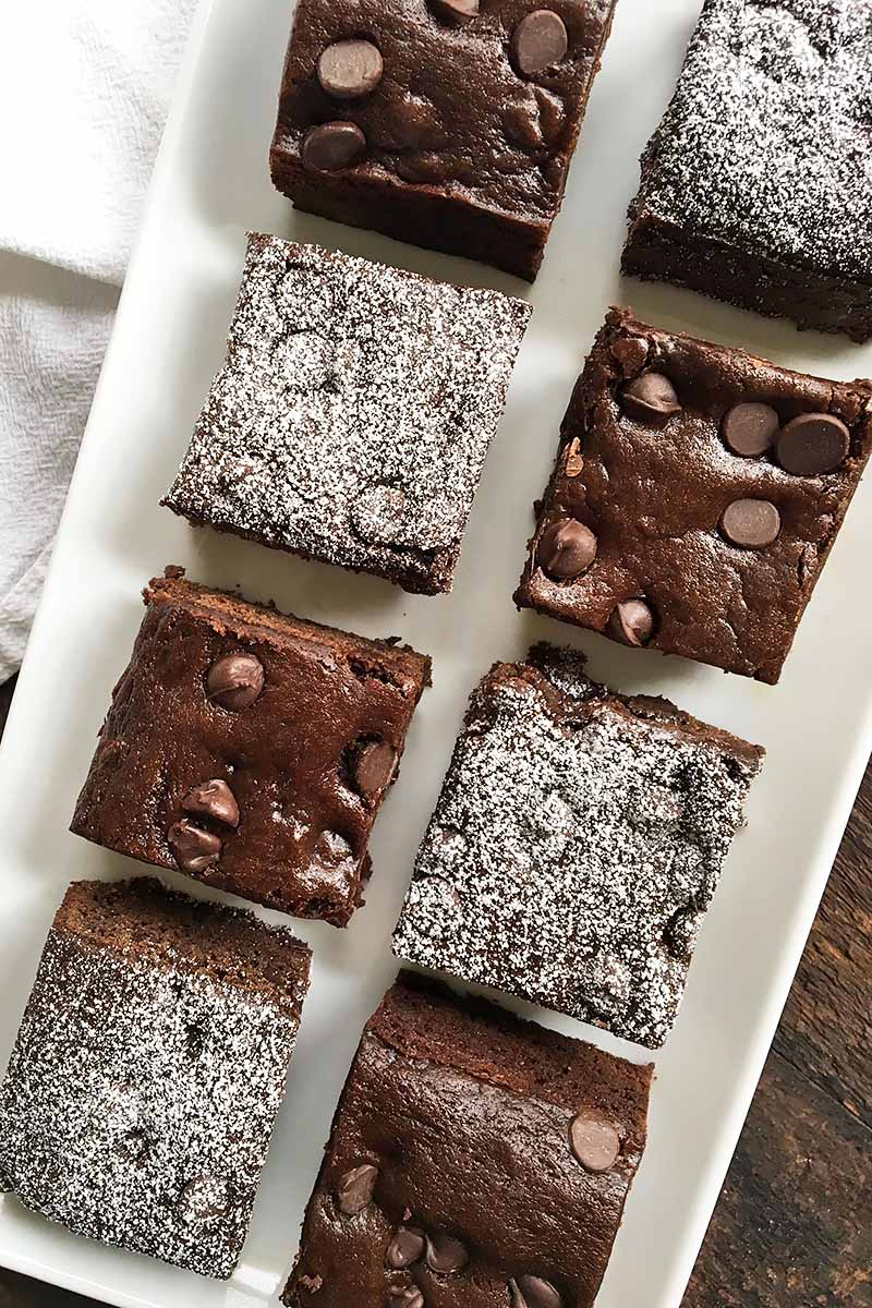 Vertical image of a white tray with alternating cake squares with and without powdered sugar.