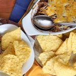 Overhead shot of an oblong ceramic dish and a plate of tortilla chips and bean dip, with a spoon and paper football-themed napkins.
