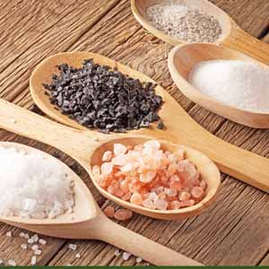 Five wooden spoons full of different types of culinary salts.