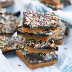A stack of five pieces of homemade lactose-free toffee with dark chocolate and toasted pecans, on a piece of parchment paper on top of a folded and gathered light blue and white cloth, with more candy in soft focus in the background.