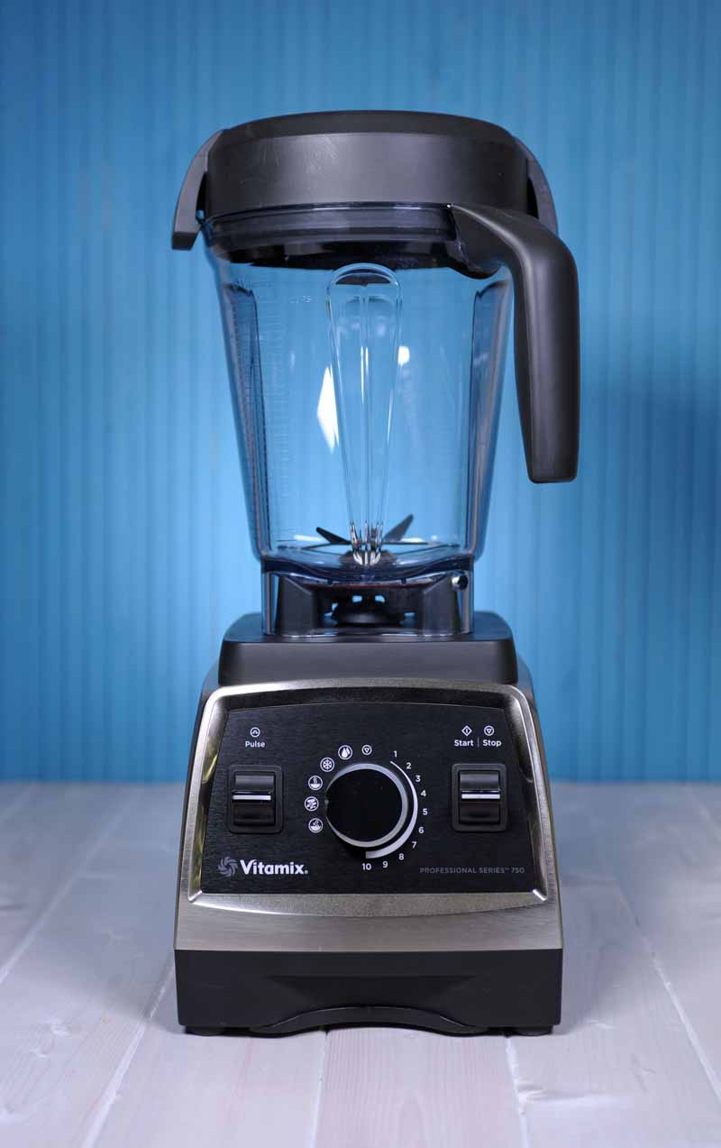 The Vitamix 750 Professional Series Blender sitting on a white painted wooden surface with a blue background.