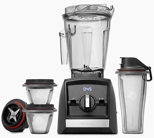 Vitamix Family Pack blender with assorted storage and blending cups and an extra blade attachment, isolated on a white background.