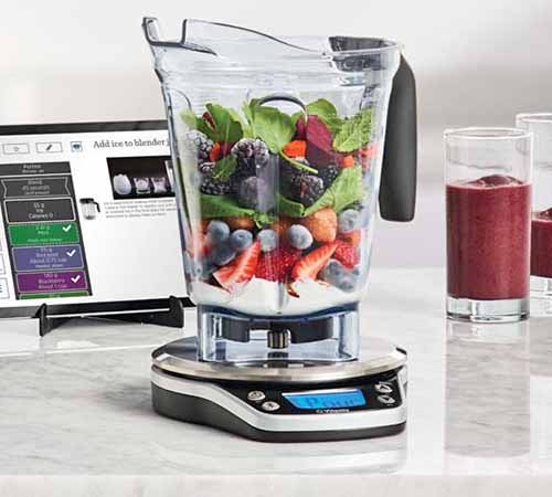 Square image of a Vitamix blender canister and scale, with a glass of purple smoothie to the right and a tablet computer on a black plastic stand in the background to the left, on a white and gray marble surface.