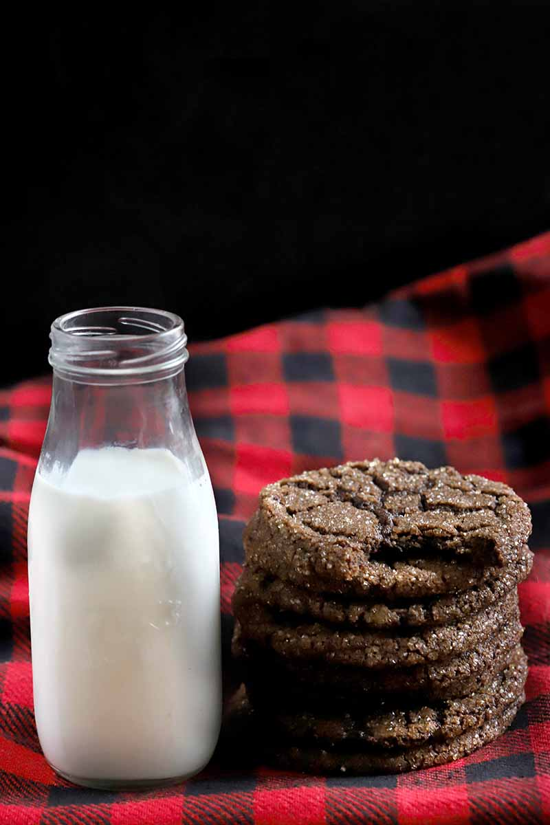 A stack of six dark chocolate cookies with a bite missing from the topmost one, to the right of a small glass bottle of milk, on a black and red plaid flannel cloth arranged at an angle, on a black background.