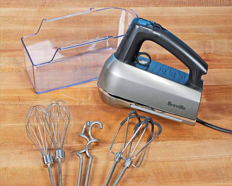 The BHM800SIL Hand Mixer Set with the soft beaters, dough hooks, and wire whisks and clear cover sitting on a maple butcher block table.