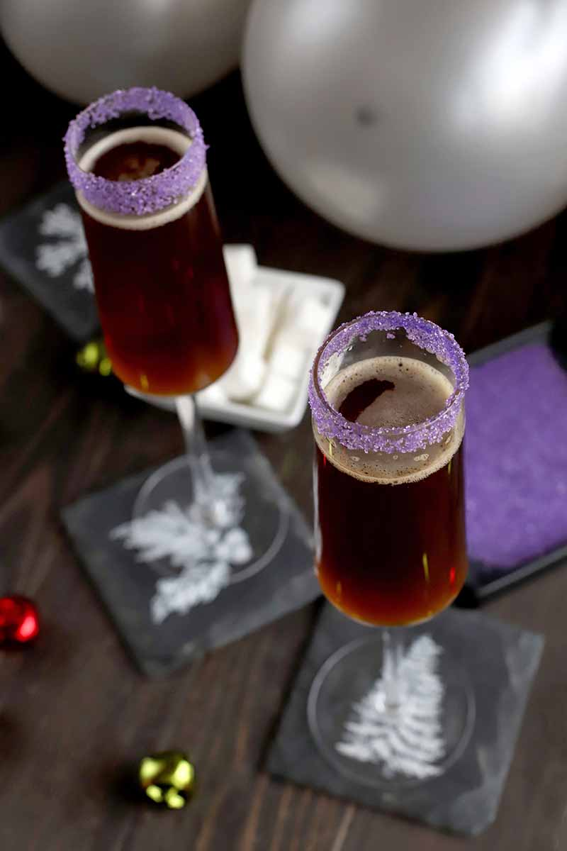 Oblique overhead shot of two tall, narrow stemware glasses filled with a brown alcoholic beverage and topped with a purple rim, on slate coasters with scattered holiday baubles, two dishes of white cubes and purple sanding sugar, and several silver balloons, on a dark brown wood table.