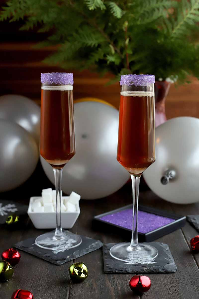 Vertical image of two cocktails on square slate coasters with scattered red and green metal jingle bells, two small dishes of white cubes and purple sanding sugar, three silver balloons, and a large maroon vase of evergreen branches, on a dark brown wood table with a lighter brown striped backdrop.