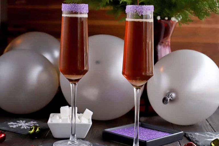 Sugar Plum Cocktails in two champagne flutes with dishes of sugar cubes and purple sanding sugar, silver balloons, and a large burgundy vase of evergreen branches in the background, against a brown backdrop.