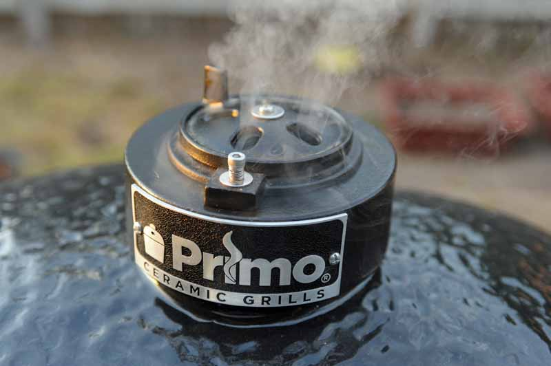 A closeup shot of the chimney cap and daisy wheel air regulator and control on the Primo XL 400.