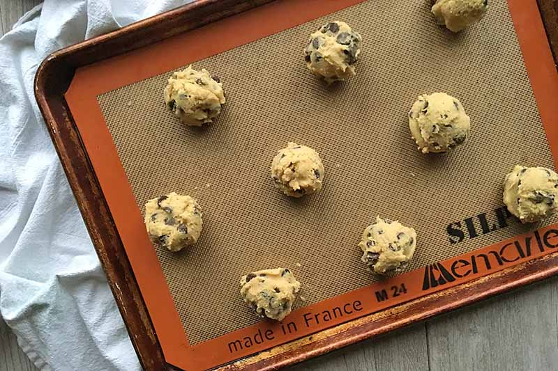 Horizontal image of mounds of unbaked dough on a baking sheet lined with a silicone mat.