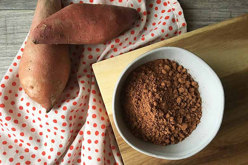 Horizontal image of cocoa powder in a white bowl next to a polka dot towel and sweet potatoes.