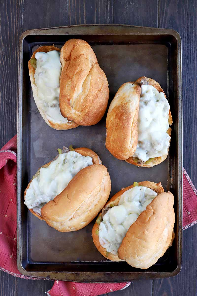 Overhead vertical shot of four homemade steak sandwiches on mini Italian rolls with melted cheese on top, on a metal baking sheet on top of a folded and gathered red cloth, on a dark brown wood surface.