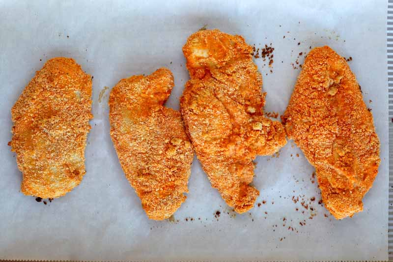 Four breaded chicken cutlets with a reddish-orange coating, on a parchment-lined baking sheet.