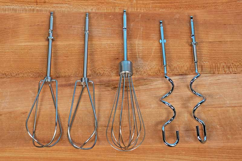 Wire beaters, wire whisk, and dough hooks on a maple wooden surface.