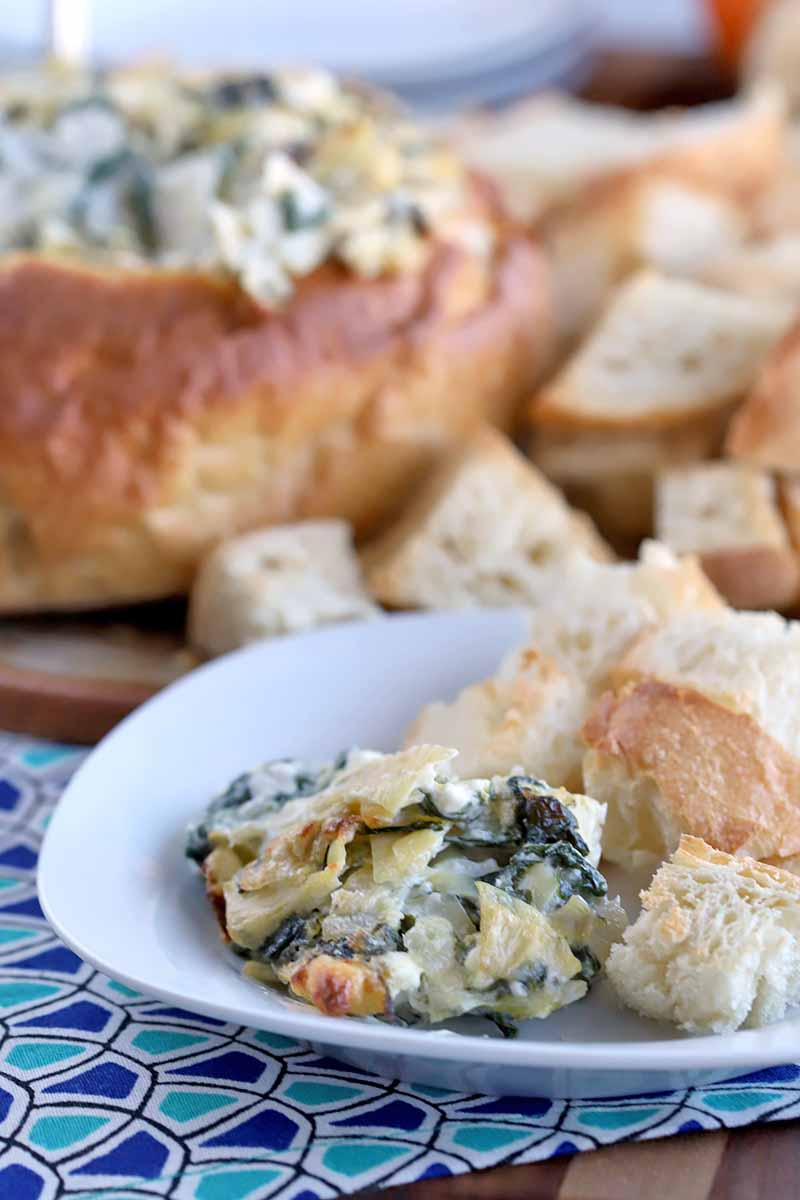 A serving of spinach artichoke dip with chunks of bread is on a white plate in the foreground, with the remainder of the dish on a platter in soft focus in the background, on a dark and light blue geometric patterned place mat on top of a striped brown wood table.