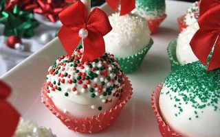 Horizontal image of white cake pops decorated with Christmas-themed colors and red bows on a white platter.