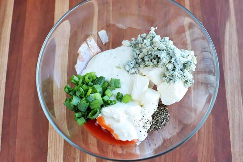 Horizontal image of ingredients for blue cheese dip in a glass bowl.