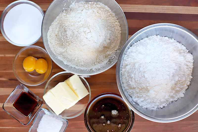 Overhead shot of all of the ingredients required to make the recipe, including bowls of flour, sugar, eggs, vanilla, butter, salt, and maple syrup, on a striped wood background.