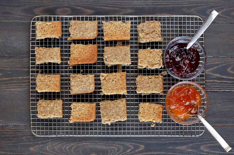 Overhead shot of 16 squares of homemade oat bars arranged in rows on a metal cooling rack with two bowls of red and orange fruit jam with spoons, on a dark brown wood surface.