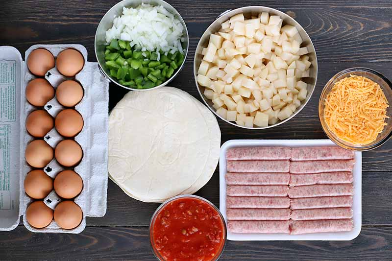 Overhead shot of an open cardboard carton of brown eggs, bowls of diced green bell pepper and onion, diced peeled potato, shreddec cheese, and salsa, a white styrofoam tray of breakfast sausage links, and a stack of flour tortillas on a dark brown wood table.