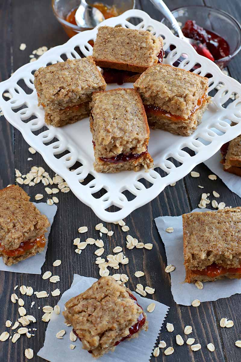 Vertical shot of homemade gluten-free oat breakfast bars with jam, arranged on a decorative white serving dish and squares of parchment paper, on a dark brown wood surface with scattered oats, and two bowls of orange and red fruit jam in the background.