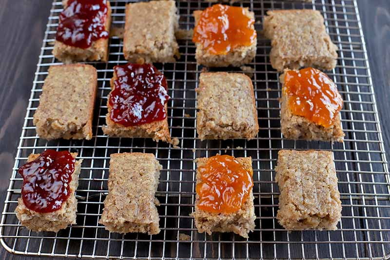 Twelve rectangular pieces of homemade oat breakfast bar, with red jam spread on three slices and orange jam on three, on a metal cooling rack on top of a dark brown wood surface.