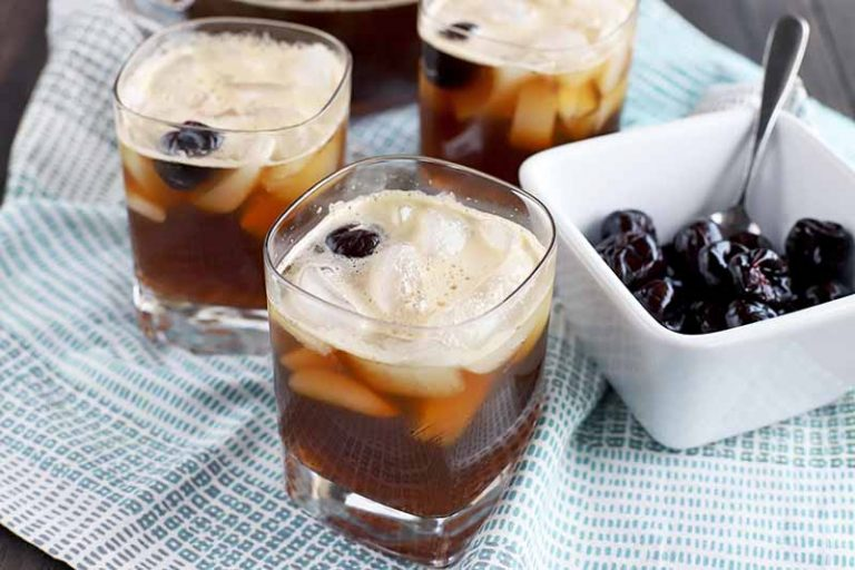 Three square lowball glasses of cherry cola beer punch garnished with maraschino cherries, with more of the preserver fruit in a small square dish to the right with a spoon, on a blue and white cloth on top of a dark brown wood surface.