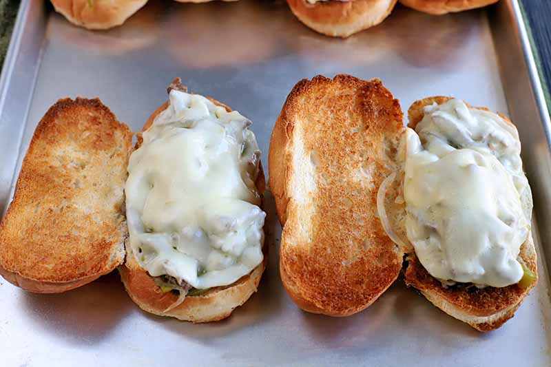 Toasted sandwich rolls topped with steak filling and melted cheese, on a baking sheet.