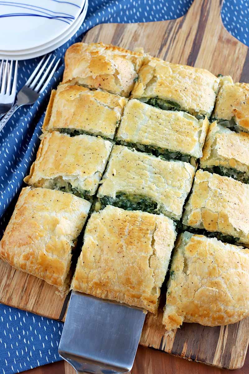 Overhead oblique shot of homemade spinach in puff pastry cut into twelve slices and arranged on a wood baking peel, with a metal spatula in the foreground removing a slice, on a blue cloth with several forks and plates, on a wood surface.