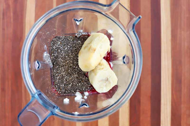 Overhead shot of two pieces of banana and chia seeds in the bottom on a clear blender pitcher, on a striped wood surface.