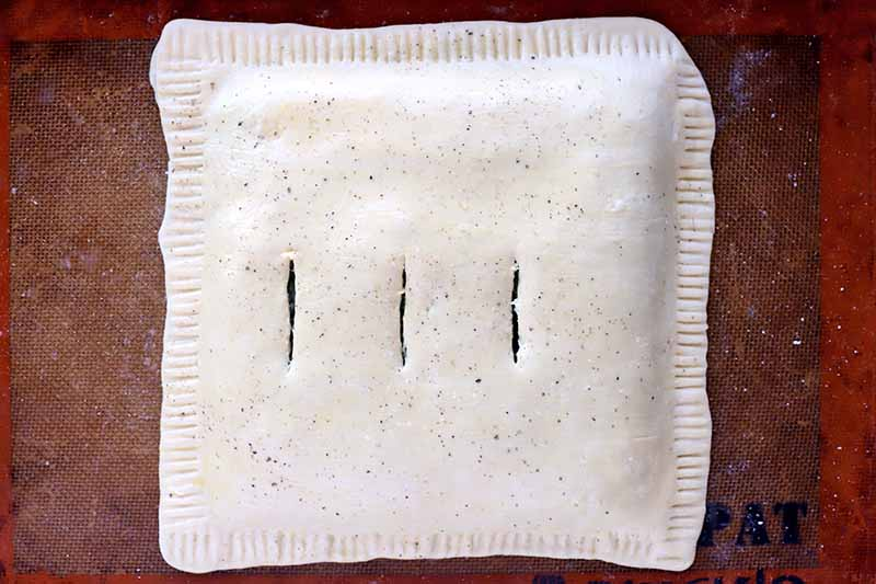 Overhead shot of a square of raw puff pastry filled with a spinach mixture, with a fluted edge and three vertical slits cut into the top, on a Silpat pan liner.