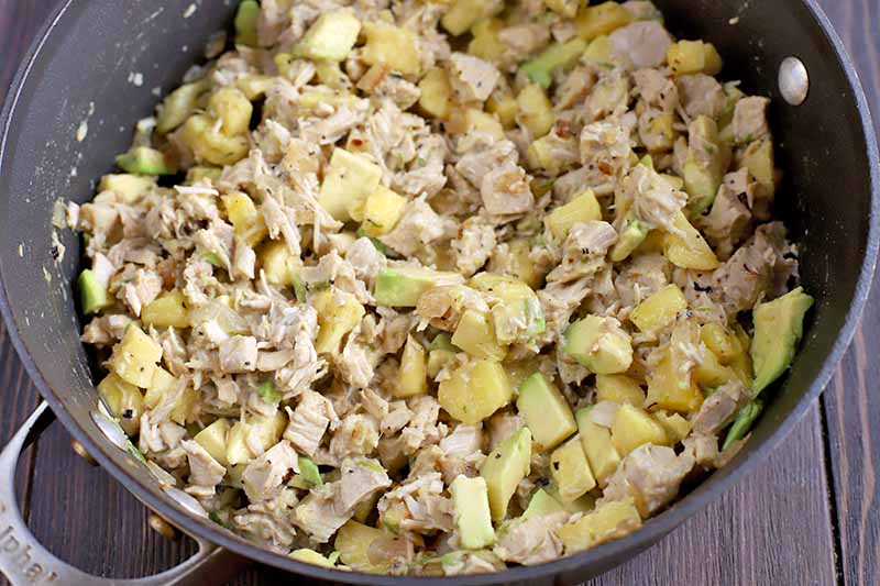 Chopped cooked chicken breast is mixed with chopped avocado and pineapple in a large frying pan, on a dark brown wood surface.