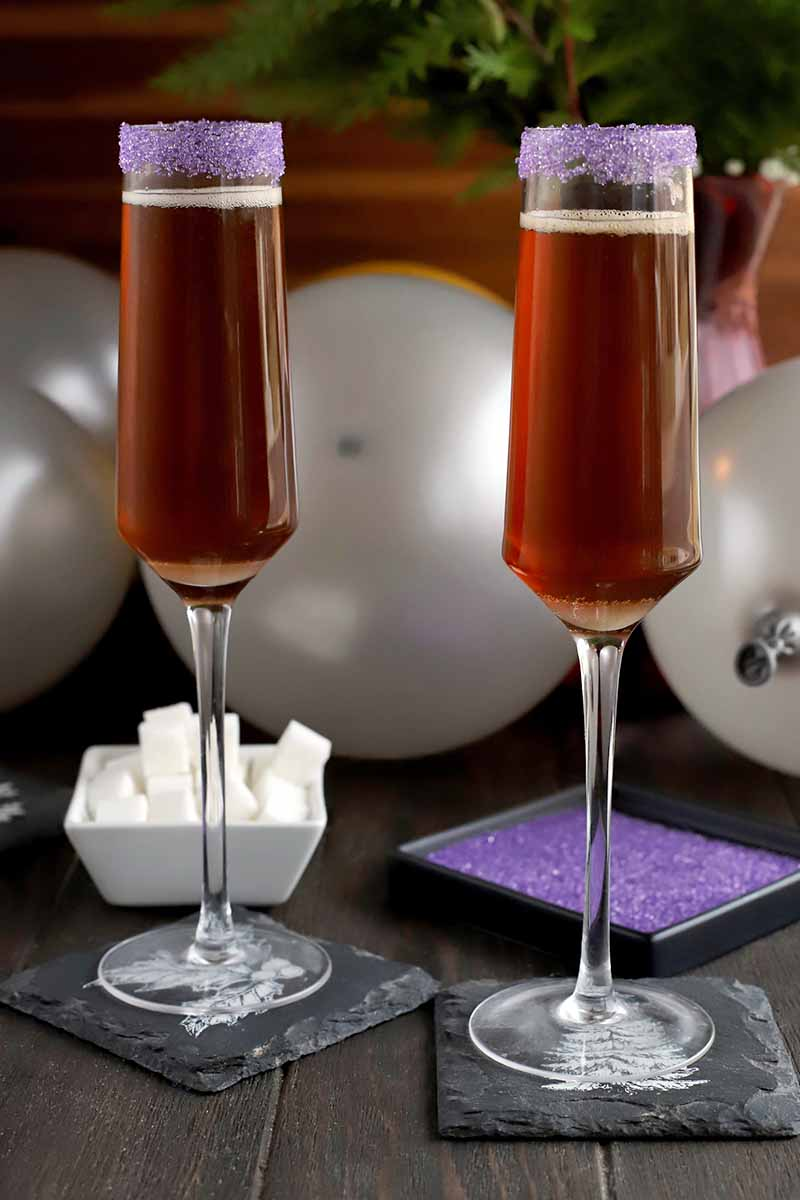 Vertical image of two cocktails on slate coasters with dishes of white cubes and purple sanding sugar with balloons and greenery in the background.