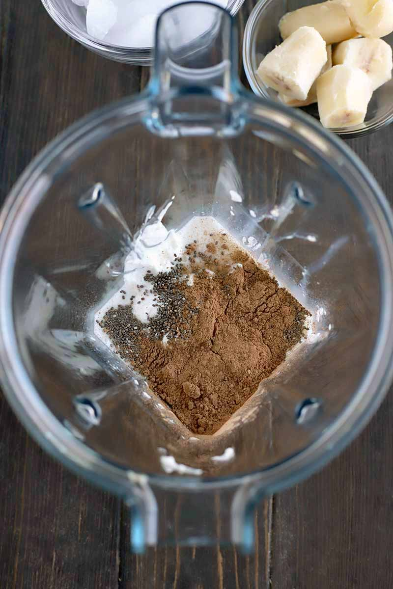 Overhead vertical shot of a clear plastic pitcher-style blender container with cocoa powder, chia seeds, and other ingredients at the bottom, with two small glass dishes of yogurt and chopped banana towards the top of the frame, on a dark brown wood table.