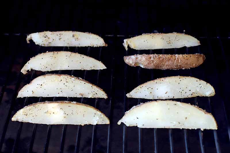 Horizontal image of potato wedges on a grill.