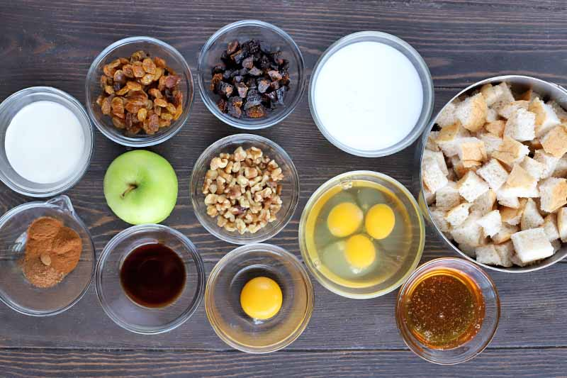Overhead shot of all of the ingredients required to make a custard-style bread pudding at home, including an apple, a bowl of cubes of bread, and smaller round glass bowls of golden raisins, chopped dried figs, cream, warming spices, cracked eggs and an extra yolk, chopped walnuts, and vanilla extract, on a dark brown wood surface.