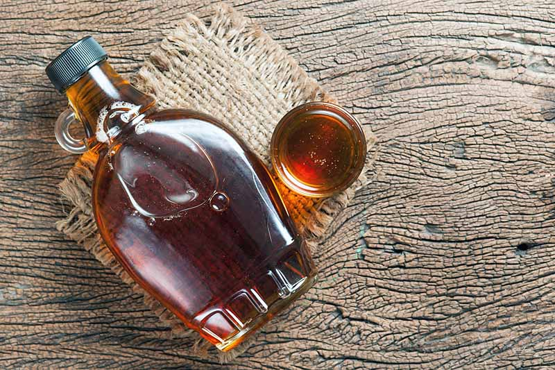Horizontal top-down image of a bottle and glass full of syrup on burlap on a wooden base.