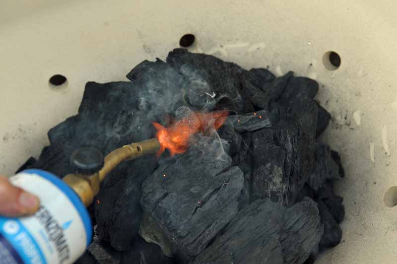 A torch is being used to light lump charcoal inside of a Primo XL 400.